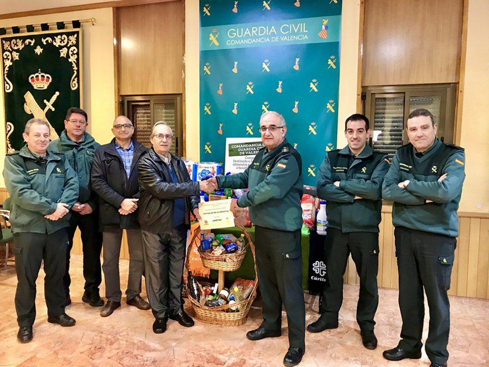 El Coronel Jefe de la Comandancia de la Guardia Civil de Valencia, Amador Escalada, hace entrega de los alimentos a Juan García, director de Cáritas de Patraix/Img. informaValencia.com